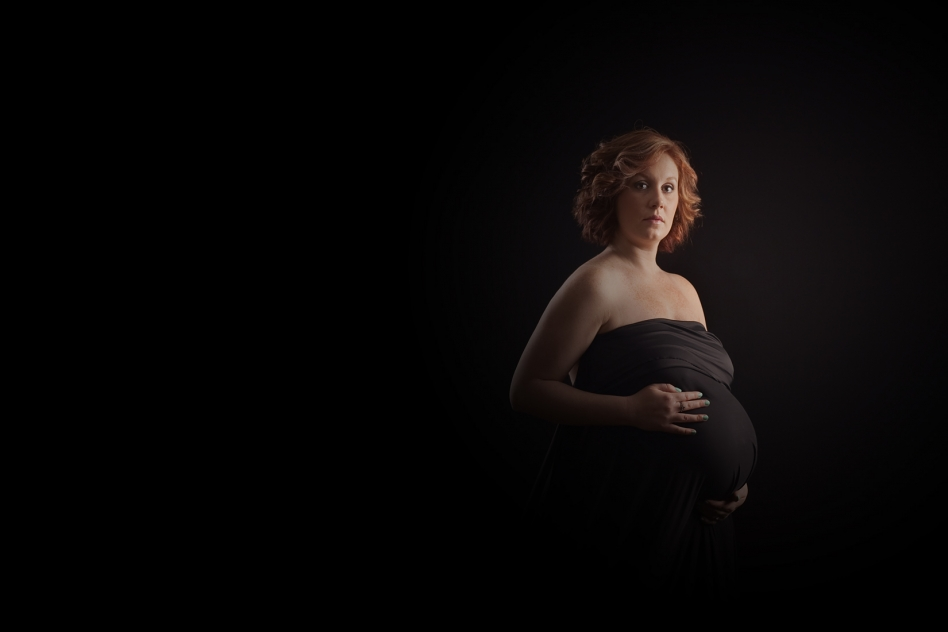 mother to be is draped in black fabric to cover her round belly while her hands softly caress her curves