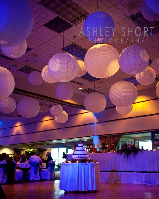 beautifully lit reception hall showcases a multi-tiered wedding cake in the middle of the room and lanterns hanging from the ceiling, creating a romantic environment