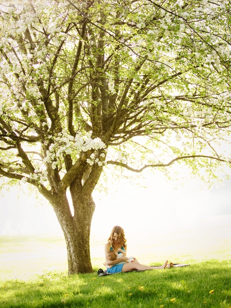 mother in blue dress smiles down at her baby while she breastfeeds under a blooming apple tree