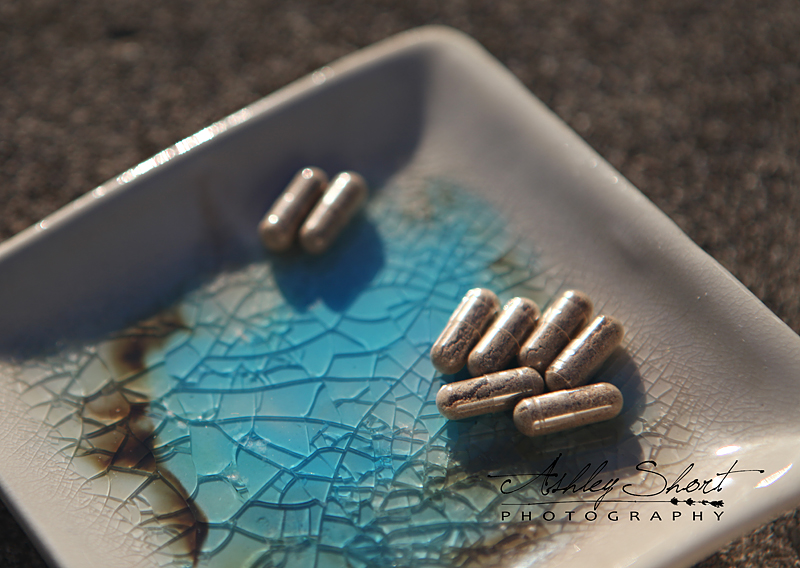 encapsulated placenta pills sit on a blue plate in the sun.