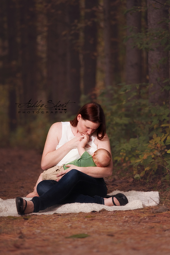 Mother breastfeeds her baby in nature, nursing in public, breastfeeding portrait in the park, mom kisses baby