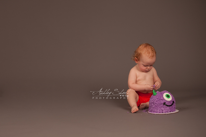 one year old baby in cloth diaper with little monitors themed smash cake,  Wauseon ohio.