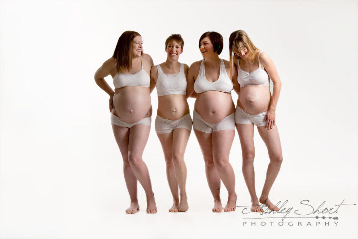 This group of 4 unique pregnant women stand together laughing in white underwear and a white background.