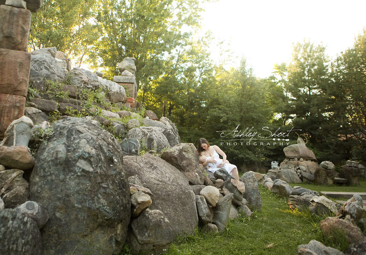 portrait of mother breastfeeding her baby on a scenic background of boulders at the Temple of Tolerance, in Wapakoneta, Ohio.